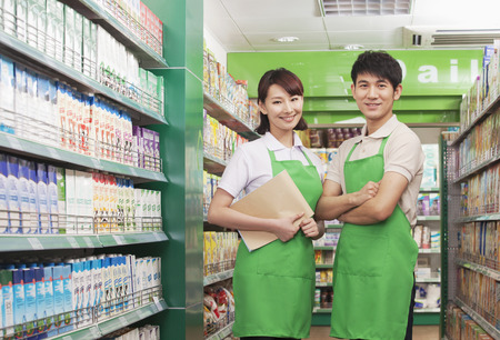 medium length hair: Two Sales Clerks Standing in a Supermarket Stock Photo