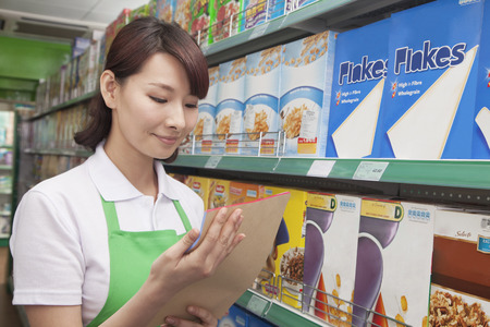 sales clerk: Female Sales Clerk Working in a Supermarket Stock Photo