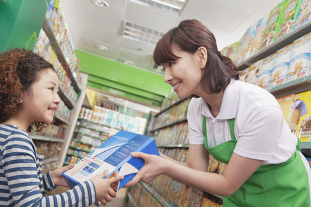 cereal box: Female Sales Clerk Gives Little Girl Cereal Box Stock Photo