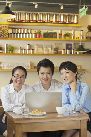 french ethnicity: Three friends sitting in coffee shop, looking at camera Stock Photo
