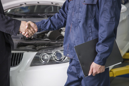 Businessman shaking hands with Mechanic in Auto Repair Shop photo