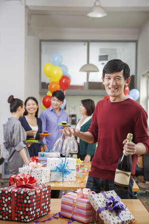 office party: Man Holding A Bottle Of Champagne and Glasses At Office Party
