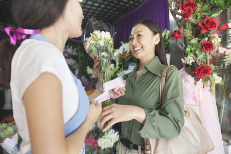small business owner: Customer Buying Bunch Of Flowers In Flower Shop