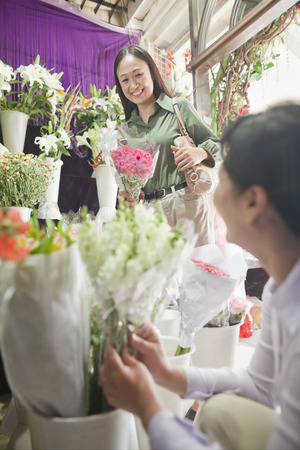 Two Mature women Looking At Flowers In Flower Shop photo