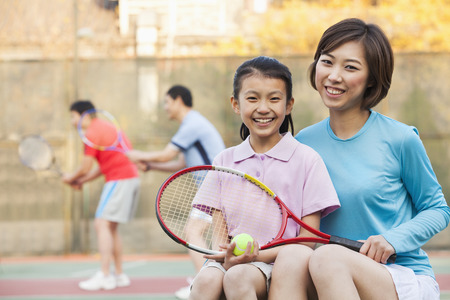 Mother and daughter playing tennis  photo