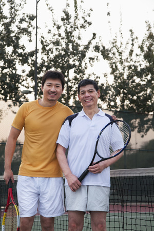Father and mature son playing tennis, portrait photo
