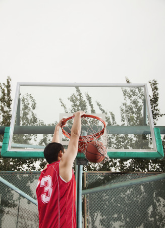 Slam dunk by young man