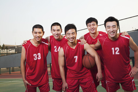 Basketball team standing and smiling, portrait photo