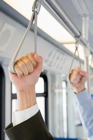 file clerks: People holding handles on train