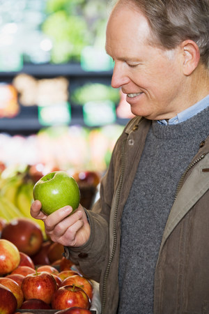 age 50 55 years: A man holding an apple Stock Photo
