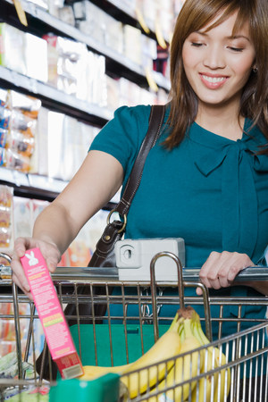grocery shopping cart: Young woman putting a packet in a shopping trolley Stock Photo