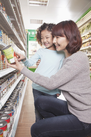 kneel down: Mother and Daughter in Supermarket Shopping, Kneeling and Looking at a Product
