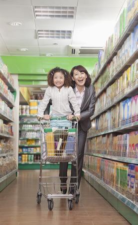 supermarket series: Mother and Daughter Having Fun in Supermarket, Pushing Cart Stock Photo