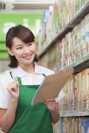sales clerk: Sales Clerk Checking Groceries in Supermarket