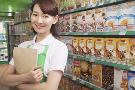 food box: Female Sales Clerk Working in a Supermarket Stock Photo