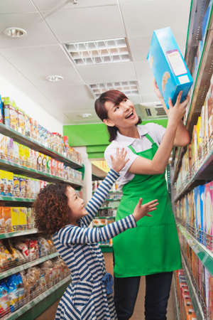 cereal box: Female Sales Clerk Helping a Little Girl Reach a Cereal Box