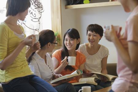 Fünf Freunde sitzen in der Kaffeestube, lesen, diskutieren