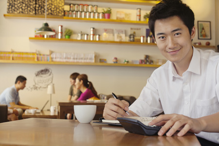 Portrait of young man working at a coffee shop photo