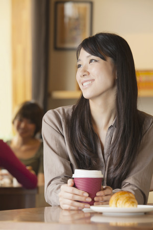 french ethnicity: Beautiful young woman sitting at a coffee shop, looking away