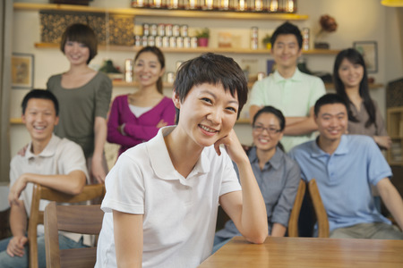 Portrait of young woman with group of friends at a coffee shop photo