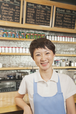 Portrait of smiling young barista in coffee shop, Beijing photo
