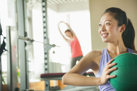 incidental people: young woman exercising in the gym