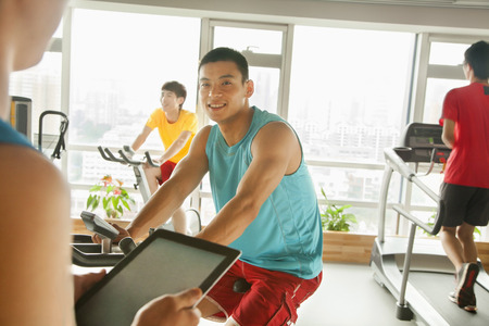 stationary bike: Young man on stationary bike exercising with his personal trainer Stock Photo