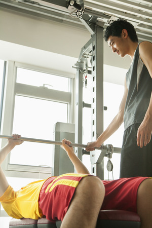 young men: Young men weight lifting with his personal trainer in the gym  Stock Photo