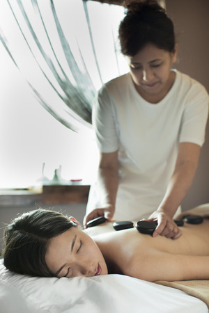 hair treatment: Young Woman Receiving Hot Stone Massage Stock Photo