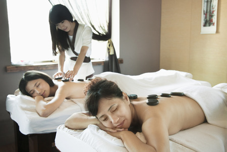 semi dress: Mother and Daughter Having Hot Stone Massage Together Stock Photo