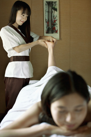 hair wrapped up: Massage Therapist Massaging Feet