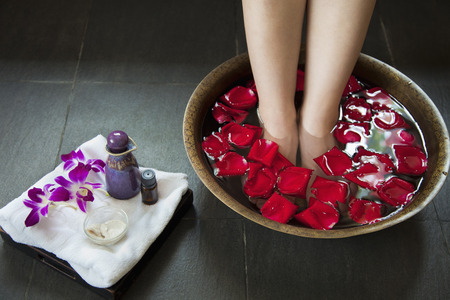 Womans Feet Soaking in Water with Rose Petals photo