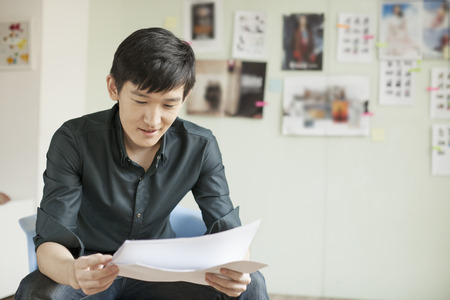 professional man: Professional Man Looking at Papers in Office
