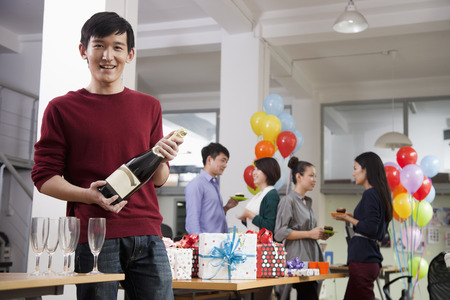 office party: Man Holding A Bottle Of Champagne At Office Party Stock Photo