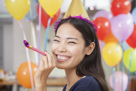 office party: Smiling Young Woman With Horn At Office Party Stock Photo