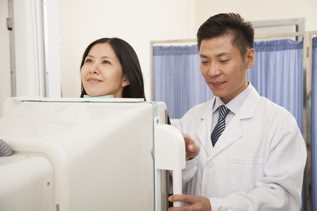 medical scanner: Male Doctor Examining Female Patients Mid Section With X-ray Machine