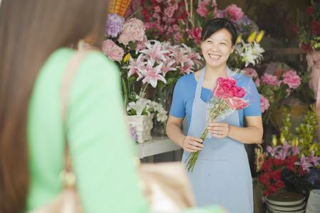 Florist Giving Bunch Of Flowers To Customer Stock Photo
