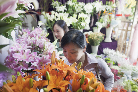 mature women: Two Mature women Looking At Flowers In Flower Shop Stock Photo