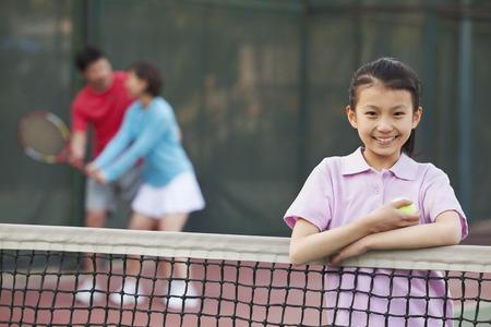 バック グラウンドで遊んで親テニスのネット、隣に立っている娘 写真素材