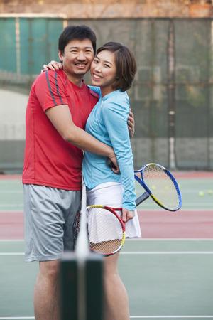 テニスのネットの横を受け入れるカップル