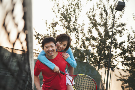 tennis net: Boyfriend holding his girlfriend next to the tennis net  Stock Photo