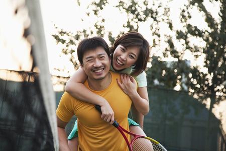 彼氏がテニスのネットの横にある彼のガール フレンドを保持 写真素材