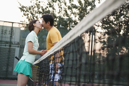 tennis net: Couple kissing over the tennis net Stock Photo