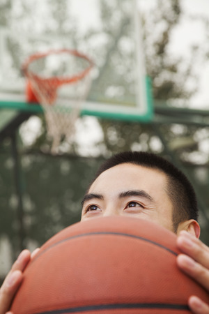 Young man covering his face with basketball  photo