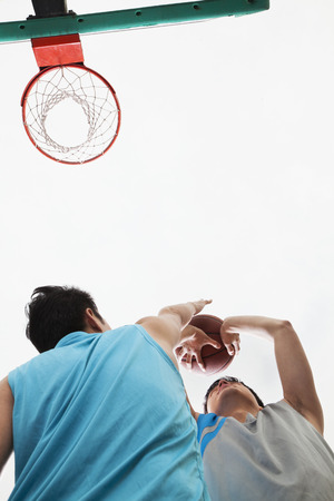 Two people playing basketball, blocking  photo