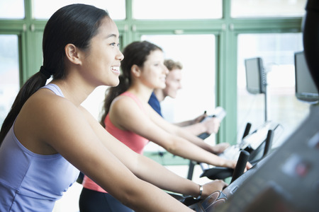 Young women exercising on fitness bikes in the gym  photo