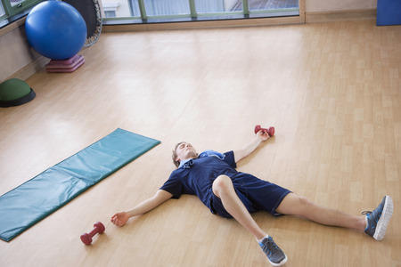tired: Tired young man lying on his back in the gym Stock Photo