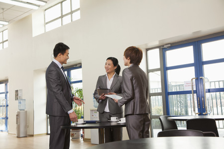 Three business people meeting in company cafeteria