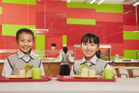 Two girls sitting in school cafeteria Foto de archivo