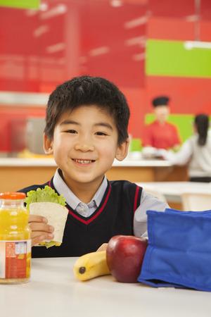 school cafeteria: School boy portrait eating lunch in school cafeteria Stock Photo